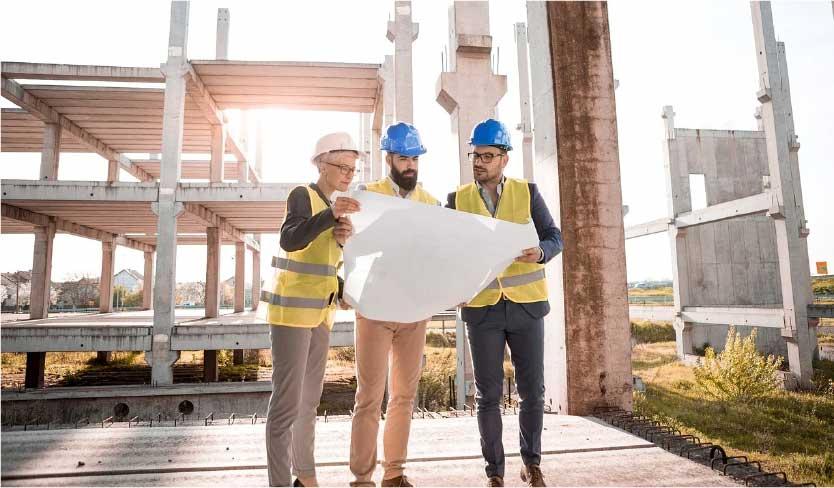Profissionais em construção em reunião discutindo o projeto