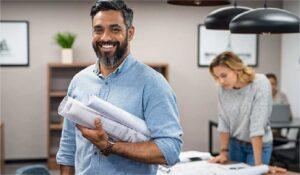 Imagem de um engenheiro em primeiro plano segurando projetos e sorrindo.